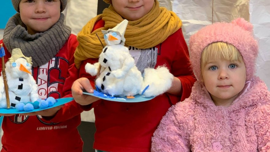 troje dzieci prezentuje własnoręcznie wykonane przez siebie bałwanki