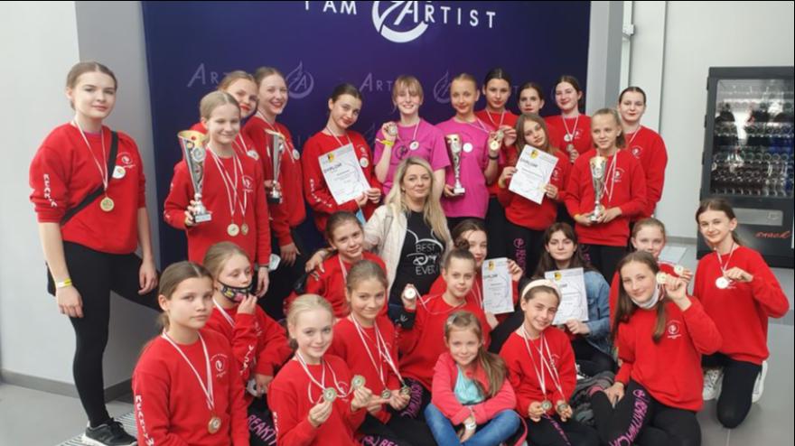 Grupa tancerek w czerwonych bluzach. Uśmiechają się i z dumą prezentują medale i dyplomy, w środku instruktorka: Ewa Rak.
